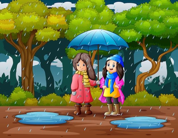 Bambini che usano l'ombrello sotto la pioggia