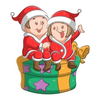 Bambini con cappotto letto seduto sul grande regalo con la faccia felice