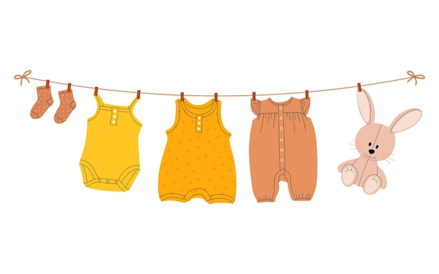 Vestiti per bambini che vengono asciugati su uno stendibiancheria con mollette