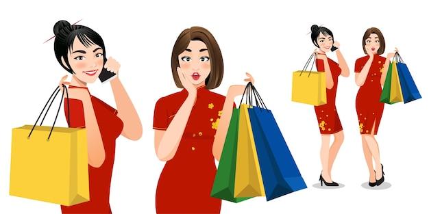 Donne cinesi in vestito cheongsam che tengono i personaggi dei cartoni animati dei sacchetti della spesa