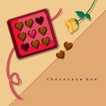 Scatola di cioccolatini sul tavolo con un paio di pezzi di cioccolato a forma di cuore e rosa gialla.