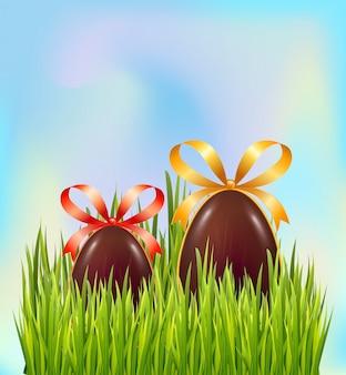 Uova di pasqua del cioccolato nascoste in erba verde sul fondo del cielo