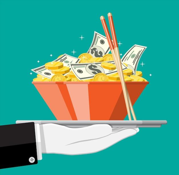 Bacchette, ciotola piena di monete d'oro e banconote in dollari. denaro, concetto di risparmio, donazione, pagamento. pranzo di lavoro. simbolo di ricchezza.