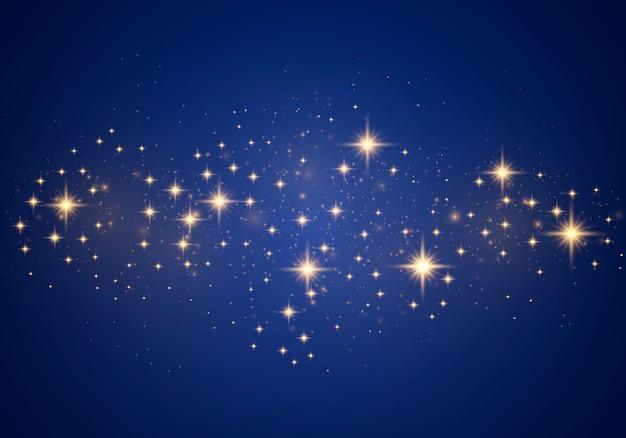 Natale astratto effetto luce elegante su uno sfondo blu. polvere gialla scintille gialle e stelle dorate brillano di luce speciale. scintille di lusso particelle di polvere magica scintillante.