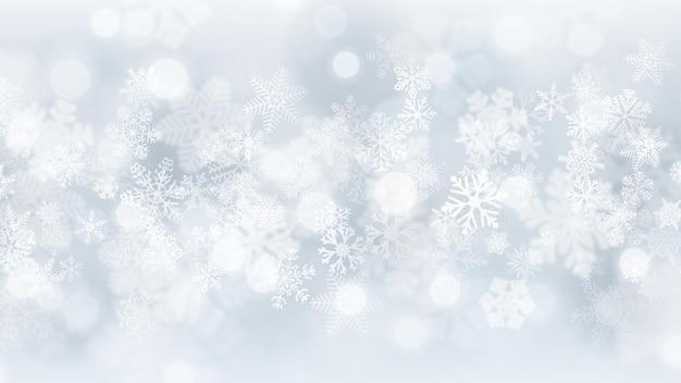 Sfondo natalizio di fiocchi di neve grandi e piccoli con effetto bokeh, nei colori bianco e grigio