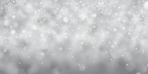 Sfondo natalizio di complessi fiocchi di neve cadenti grandi e piccoli in colori grigi con effetto bokeh