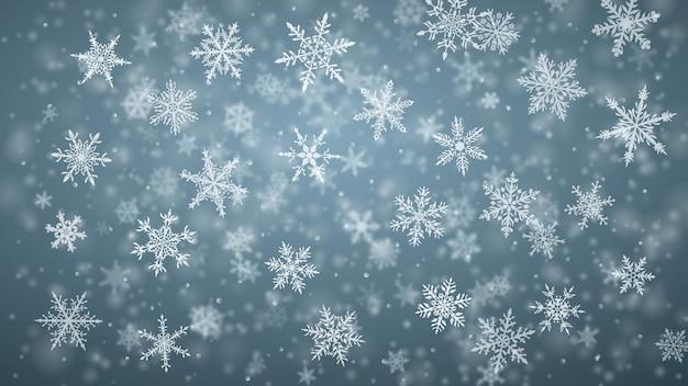 Sfondo natalizio di complessi fiocchi di neve che cadono sfocati e chiari in colori grigi con effetto bokeh