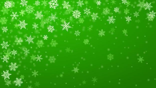 Sfondo natalizio di complessi fiocchi di neve che cadono sfocati e chiari in colori verdi con effetto bokeh