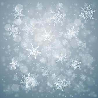 Sfondo natalizio di complessi fiocchi di neve che cadono sfocati e chiari in colori blu chiaro con effetto bokeh