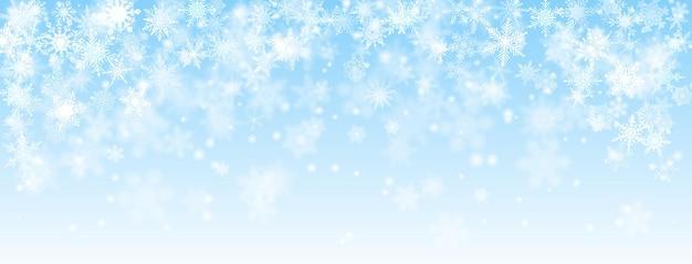Sfondo di natale di fiocchi di neve che cadono in colori blu chiaro