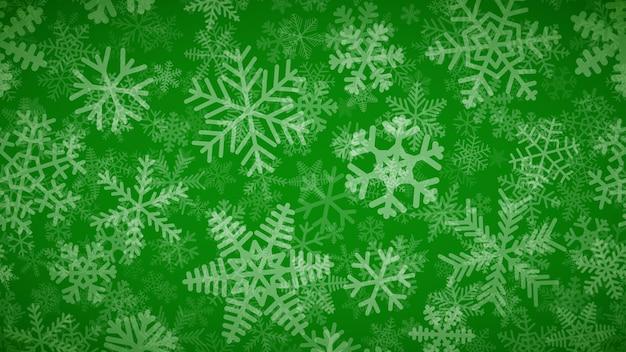 Sfondo natalizio di molti strati di fiocchi di neve di diverse forme, dimensioni e trasparenza. bianco su verde.