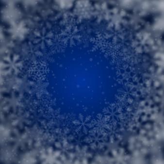 Sfondo natalizio di fiocchi di neve di diversa forma, sfocatura e trasparenza, disposti in cerchio, su sfondo blu