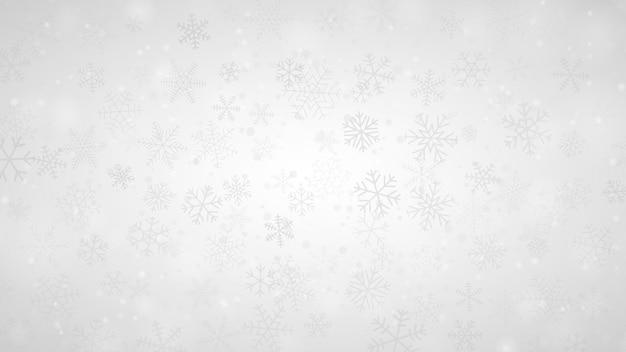Sfondo natalizio di fiocchi di neve di diverse forme, dimensioni e trasparenza nei colori grigio e bianco