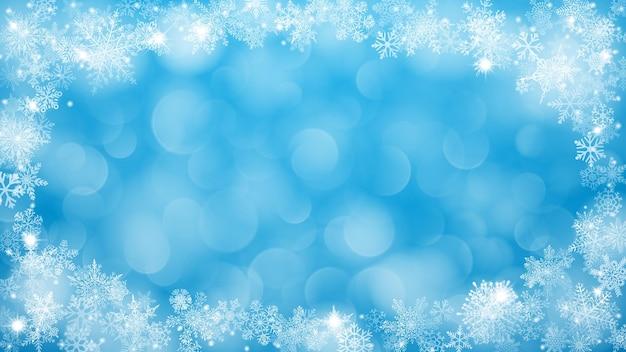 Sfondo natalizio con cornice di fiocchi di neve a forma di ellisse nei colori blu e con effetto bokeh