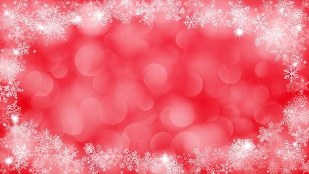 Sfondo natalizio con cornice di fiocchi di neve a forma di ellisse nei colori rossi e con effetto bokeh
