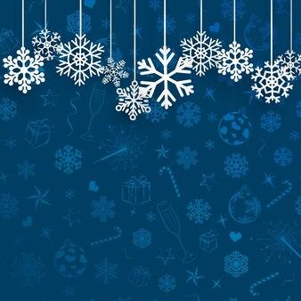 Sfondo di natale con fiocchi di neve appesi su sfondo blu di simboli natalizi