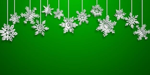 Sfondo natalizio con fiocchi di neve di carta appesi con ombre morbide su sfondo verde