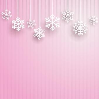 Sfondo di natale con diversi fiocchi di neve appesi su sfondo a strisce rosa