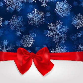 Sfondo di natale con fiocchi di neve nei colori blu e grande fiocco rosso con nastri orizzontali