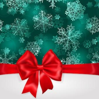 Sfondo natalizio con fiocchi di neve in colori turchesi e grande fiocco rosso con nastri orizzontali