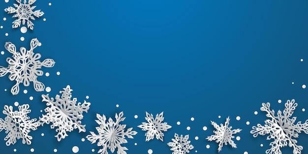Sfondo di natale con fiocchi di neve di carta volume con ombre morbide su sfondo blu