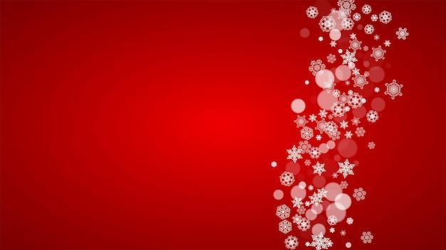 Sfondo di natale con fiocchi di neve bianchi su sfondo rosso. i colori di babbo natale. sfondo di capodanno e natale per invito a una festa, banner, carta regalo, offerta al dettaglio. sfondo invernale orizzontale