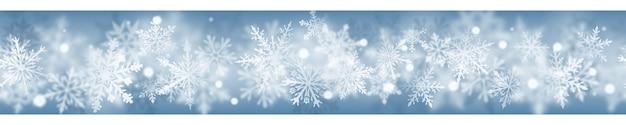 Banner di natale di complessi fiocchi di neve sfocati e chiari nei colori bianchi su sfondo azzurro. con ripetizione orizzontale