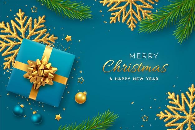 Banner di natale. scatola regalo blu realistica con fiocco dorato, fiocco di neve splendente, stelle dorate, rami di pino