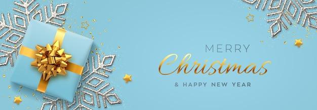 Banner di natale. scatola regalo blu realistica con fiocco dorato, fiocco di neve brillante argento, stelle dorate e coriandoli glitterati.