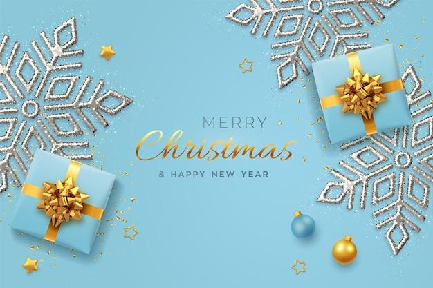 Banner di natale. scatole regalo blu realistiche con fiocco dorato, fiocco di neve splendente, stelle dorate e coriandoli glitter, palline. natale