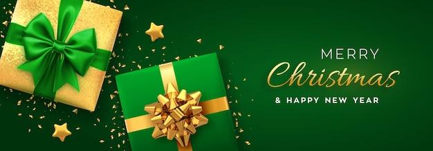 Banner di natale scatole regalo realistiche con fiocco verde e dorato, stelle dorate e glitter