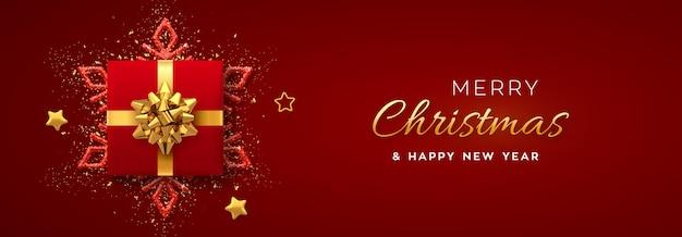 Banner di natale. scatola regalo rossa realistica con fiocco dorato, fiocco di neve splendente, stelle dorate e coriandoli glitterati.
