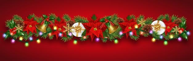 Ghirlanda di decorazioni natalizie con rami di abete, stella di natale con fiori di natale, campanelli d'oro, bacche di agrifoglio e scatole regalo.