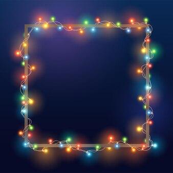 Ghirlanda di natale di colore brillante su cornice quadrata. modello con luci realistiche su sfondo blu