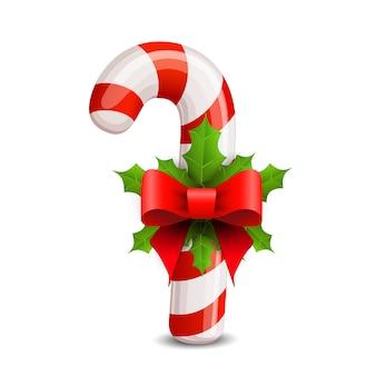 Bastoncino di zucchero natalizio decorato con un fiocco e un agrifoglio.