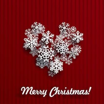 Cartolina di natale con cuore fatto di fiocchi di neve bianchi su sfondo a strisce rosse