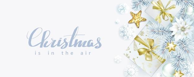 Composizione natalizia con rami di abete e scatole regalo su sfondo bianco