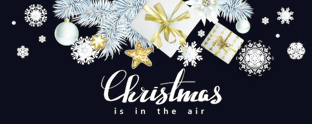 Composizione natalizia con rami di abete bianco e scatole regalo su sfondo nero
