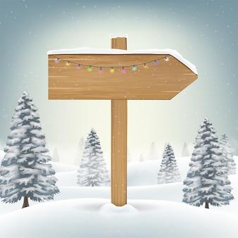 Segno di bordo di legno di direzione di natale sulla neve