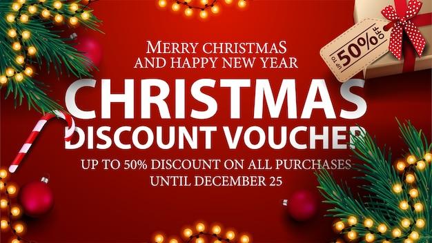 Buono sconto natalizio, fino al 50% su tutti gli acquisti. buono sconto rosso con regali, rami di albero di natale, bastoncini di zucchero e palle di natale