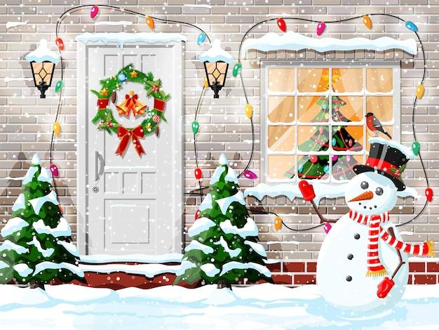 Decorazione della facciata di natale con pupazzo di neve e alberi