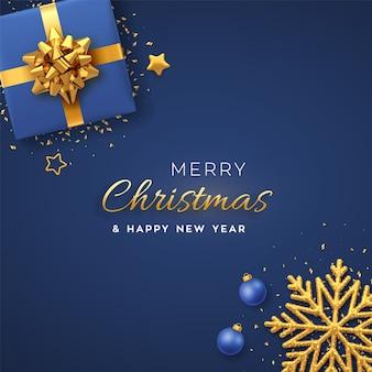Biglietto di auguri di natale. scatola regalo blu realistica con fiocco dorato, fiocco di neve brillante, stelle dorate e coriandoli glitterati, palline. natale