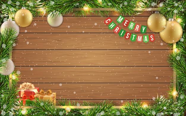 Biglietto di auguri di natale con cornice di abete, palla di natale dorata e spazio per testo di congratulazioni su fondo in legno con fiocchi di neve.