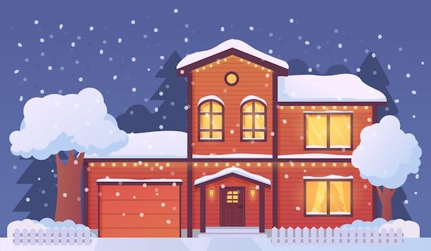 Casa di natale decorata con le luci di via luminose e coperta da neve ,. paesaggio rurale di inverno con gli abeti nella neve.