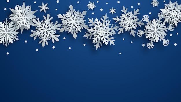 Illustrazione natalizia di fiocchi di neve di carta bianchi complessi con ombre morbide su sfondo blu