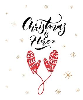 Natale è qui. didascalia di calligrafia e guanti disegnati a mano rossi su sfondo bianco.