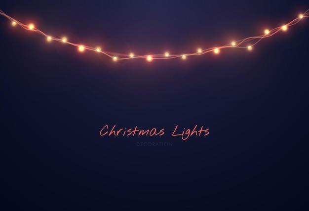 Le luci di natale isolate su ghirlande nere si illuminano con lampadine su fili metallici