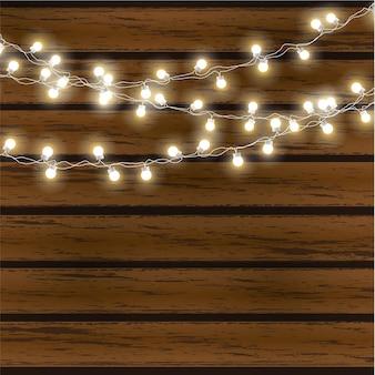 Luci di natale isolate su fondo di legno scuro. ghirlanda luminosa.