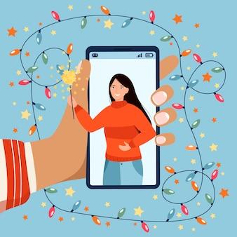 Natale nuovo concetto normale con mano che tiene il telefono durante la videochiamata. festa di natale in linea.