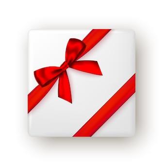 Confezione regalo di natale capodanno con nastro rosso e fiocco vista dall'alto Vettore Premium